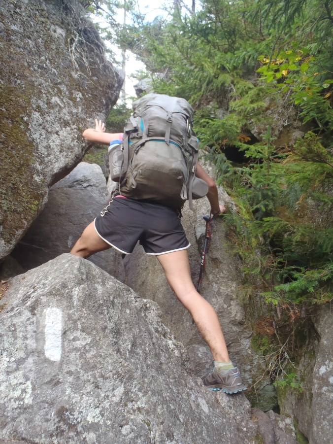 Lindsay squeezing over, under and through rocks in the Mahoosuc Notch