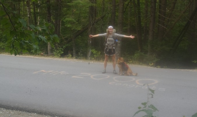 Lindsay at the historic and iconic 2,000mi mark painted on an unknown road in northern Maine