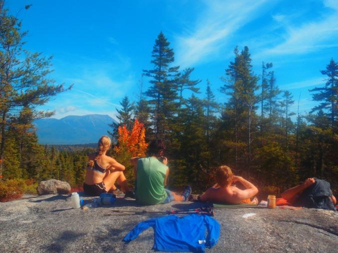 Lindsay, Turtle, Sunshine and Fern Gully enjoying the warm rocks with a view of Katahdin